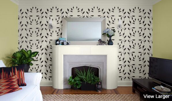 A wall stencilled with Benjamin Moore's Vineyard Wall Tattoo frames a fireplace.